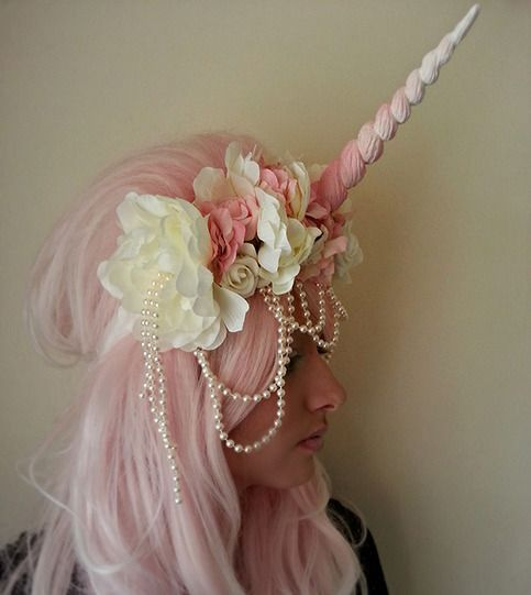 A Head Dress Adorned With A Plastic Resin Unicorn Horn And Dressed